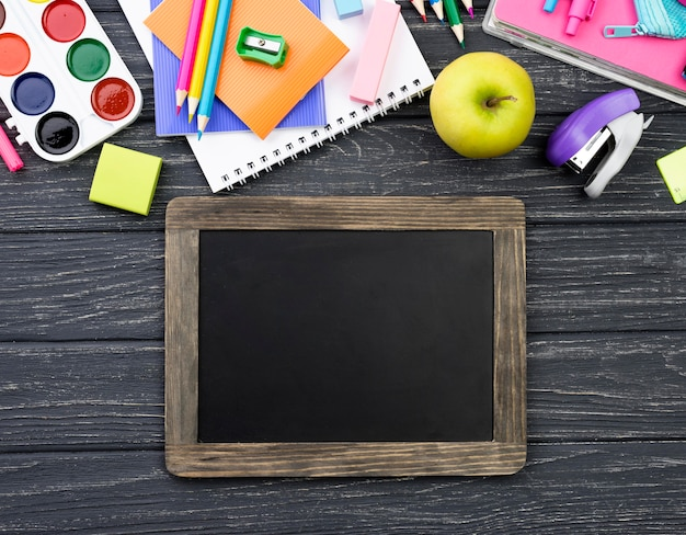 Top view of back to school stationery with blackboard and apple
