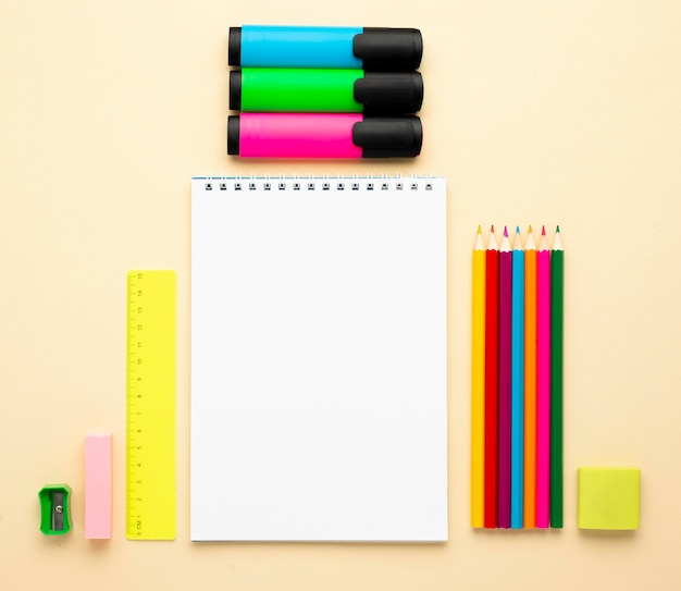 Top view of back to school stationery with colored pencils and notebook