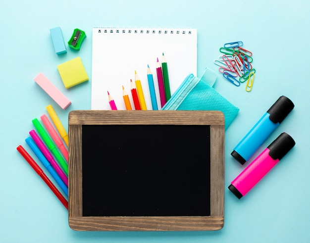 Top view of back to school stationery with colorful pencils and blackboard