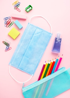 Top view of back to school stationery with colorful pencils and medical mask