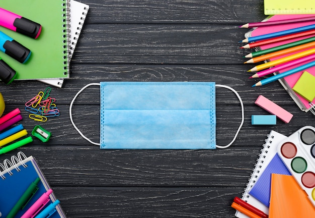Top view of back to school stationery with face mask and colorful pencils