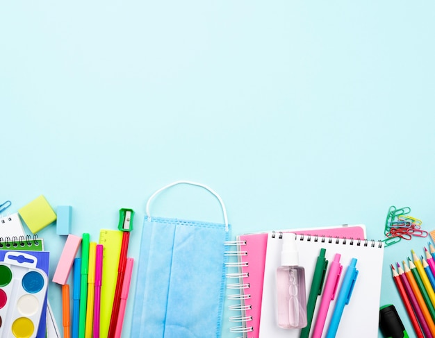 Top view of back to school stationery with medical mask and copy space