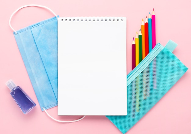 Top view of back to school stationery with notebook and medical mask