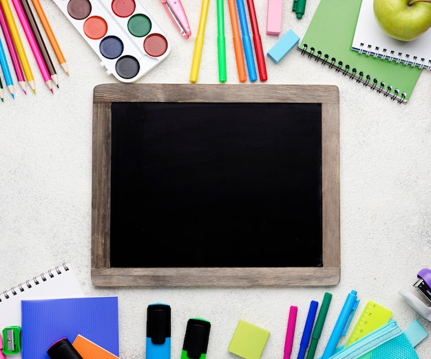 Top view of back to school supplies with blackboard and colorful pencils