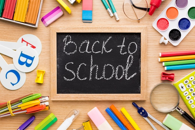 Top view of back to school supplies with blackboard and glasses