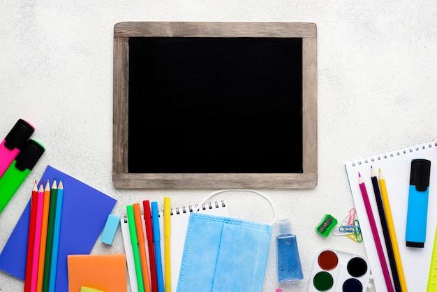 Top view of back to school supplies with blackboard and pencils