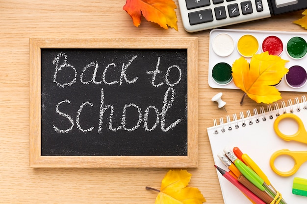 Top view of back to school supplies with blackboard