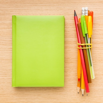 Top view of back to school supplies with book and pencils