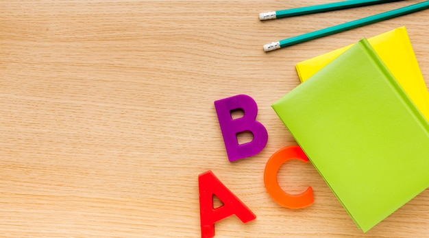Top view of back to school supplies with books and letters