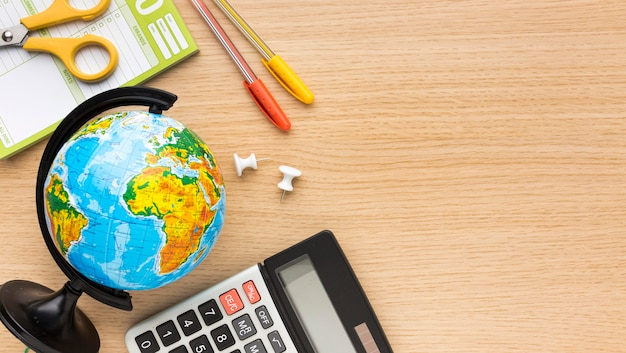 Top view of back to school supplies with calculator and globe