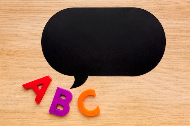 Top view of back to school supplies with chat bubble and letters