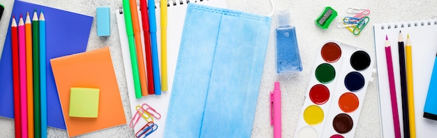 Top view of back to school supplies with face mask and watercolor