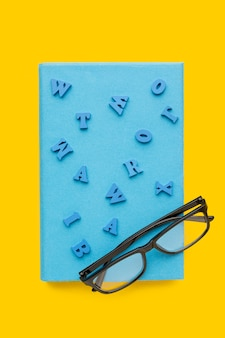 Top view of back to school supplies with glasses on book and letters