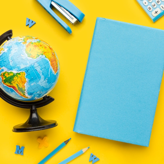Top view of back to school supplies with globe and book