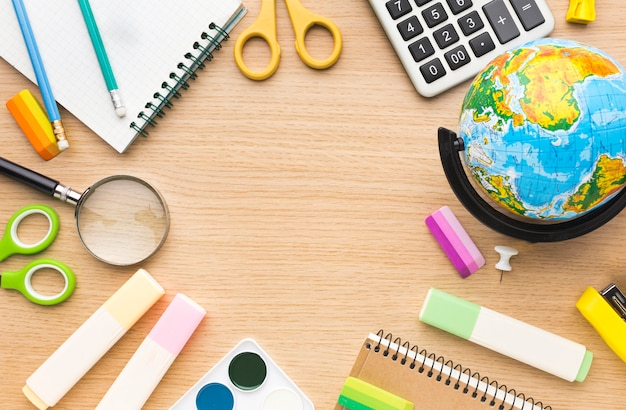 Top view of back to school supplies with globe and scissors