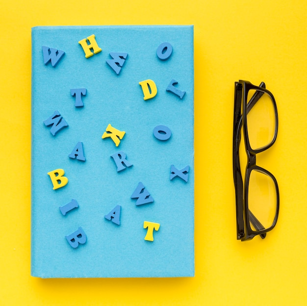 Top view of back to school supplies with letters on book and glasses