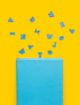 Top view of back to school supplies with letters and book