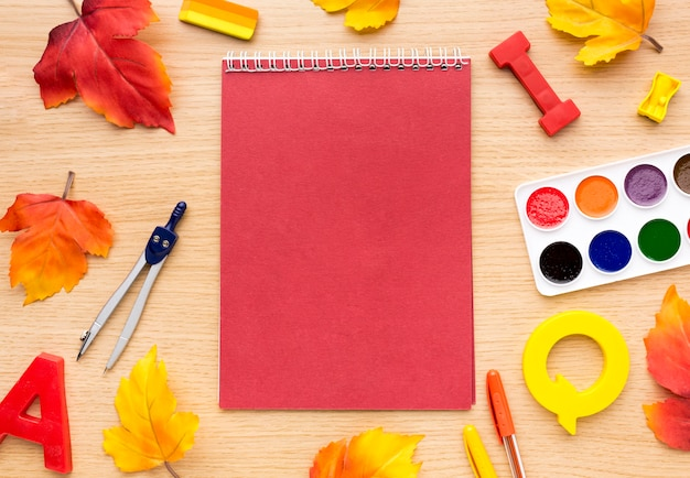 Top view of back to school supplies with notebook and leaves