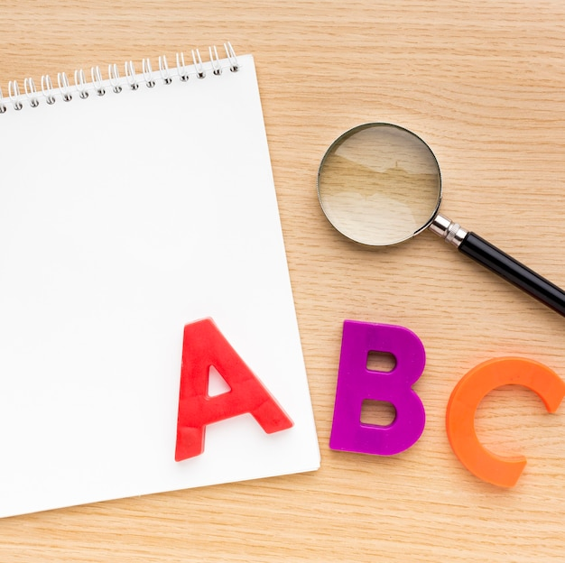 Top view of back to school supplies with notebook and letters