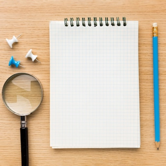 Top view of back to school supplies with notebook and magnifying glass