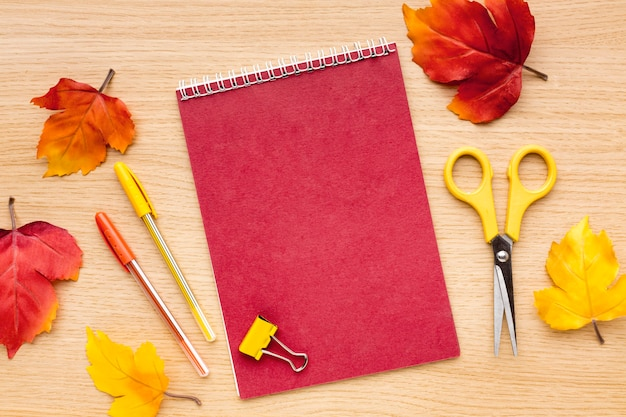 Top view of back to school supplies with notebook and scissors