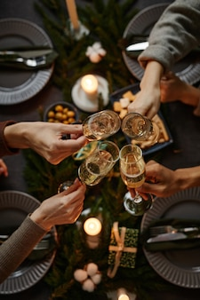 Top view background of four people enjoying christmas dinner together and toasting with champagne gl...