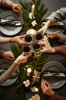 Top view background of four people enjoying christmas dinner together and toasting with wine glasses...