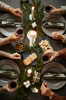 Top view background of four people enjoying christmas dinner together while sitting by elegant dinin...
