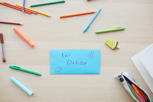 Top view background image of letter for dad with handmade gift on fathers day set on table with colored crayons, copy space