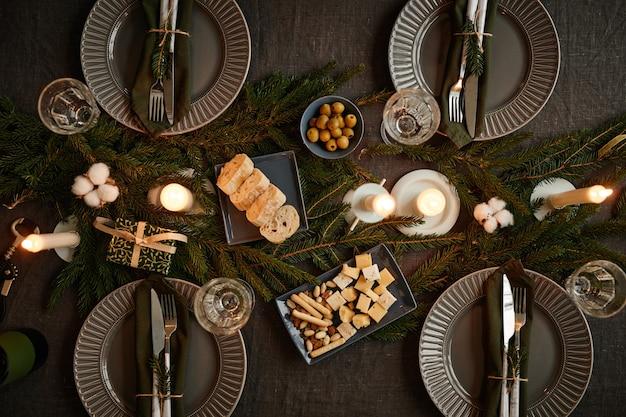 촛불이 켜진 복사 공간으로 크리스마스를 위해 장식된 검정 테이블 설정의 상위 뷰 배경 이미지