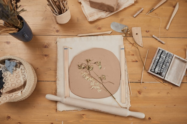 Top view background image of raw plant imprint ceramics on wooden table with tools in pottery workshop, copy space