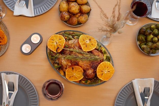 友人や家族とのディナーパーティーの準備ができている感謝祭のテーブルでおいしいローストチキンの上面図の背景