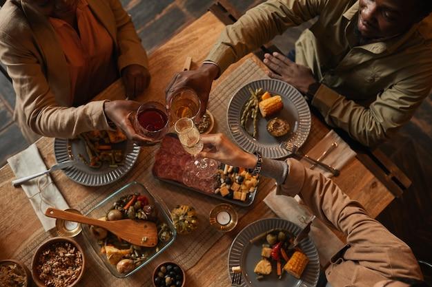 Вид сверху многоэтнической группы людей, наслаждающихся застольем во время званого ужина с друзьями и семьей