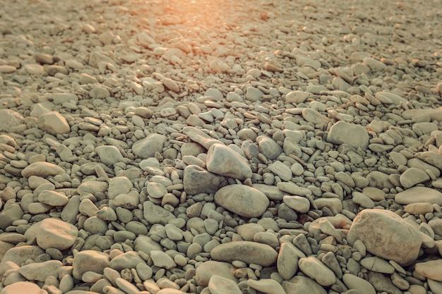 Предпосылка вида сверху округлой гальки на пляже. обработка в стиле ретро или винтаж для дизайна и творчества камешки на солнышке. путешествие в грузию