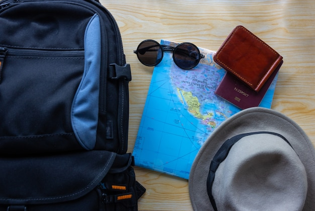 Top view of  backpack bag with other travel accessories on wooden