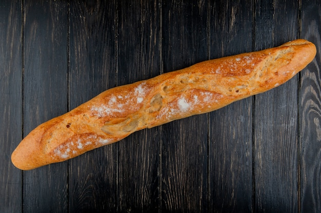 Top view of baguette on wooden background