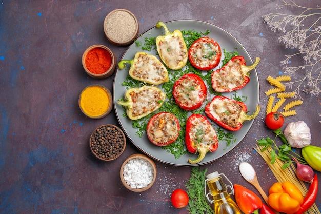 Vista dall'alto di peperoni al forno delizioso pasto con carne all'interno e condimenti su sfondo scuro pasto cena cibo piatto da forno