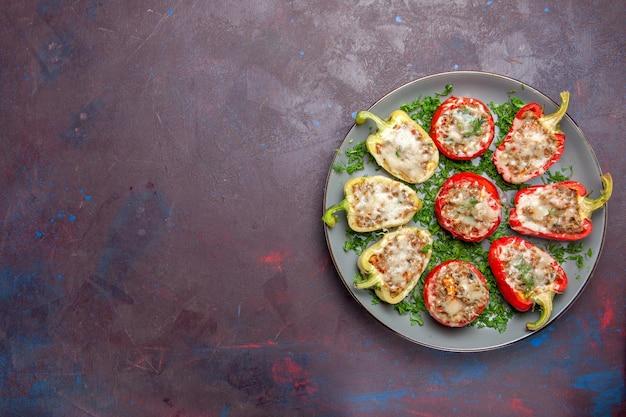 暗い背景のプレートの内側にチーズグリーンと肉が入った上面焼きピーマンは、夕食料理の食事を焼きます