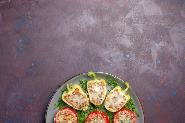 Vista dall'alto peperoni al forno con verdure al formaggio e carne all'interno del piatto sullo sfondo scuro cuocere il pasto del piatto della cena