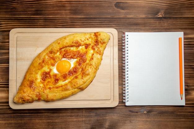 木の表面に調理された卵とメモ帳が付いた上面図焼きたてパンパン食品朝食生地