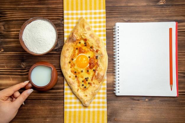 테이블 빵 과자 롤빵 아침 식사에 요리 계란 우유와 밀가루와 상위 뷰 구운 빵