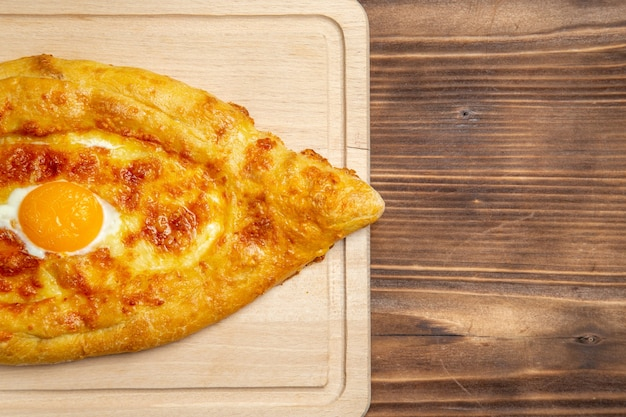 Вид сверху испеченный хлеб с вареным яйцом на коричневой деревянной поверхности хлебная булочка еда яйцо тесто для завтрака
