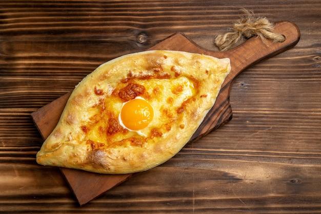 上面図木の表面のパン生地パンの朝食に調理された卵と焼きたてのパン
