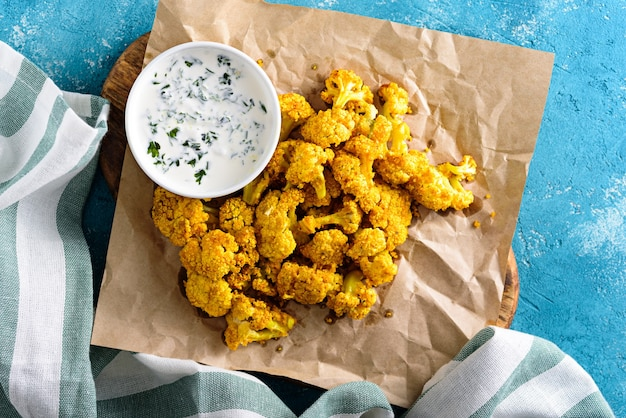 Top view baked cauliflower with spices and sour cream sauce on parchment paper on blue background. healthy vegetable snack concept