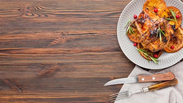 Вид сверху запеченный цыпленок и дольки апельсина на тарелке со столовыми приборами и копией пространства