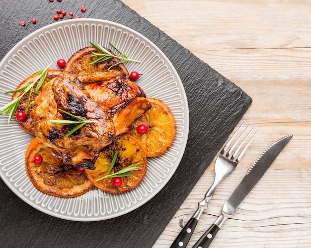 Вид сверху запеченной курицы и дольками апельсина на тарелке со столовыми приборами
