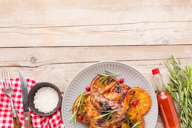 Вид сверху запеченный цыпленок и дольки апельсина на тарелке с морской солью и соусом