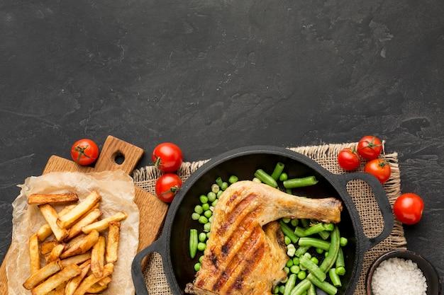 Вид сверху запеченная курица и стручки гороха на сковороде с картофелем и помидорами с копией пространства