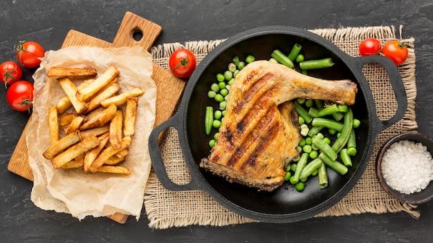 Вид сверху запеченная курица и стручки гороха на сковороде с картофелем и помидорами