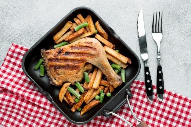 Вид сверху запеченный цыпленок и картофель на сковороде со столовыми приборами